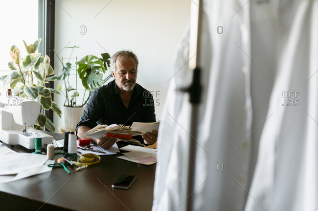 Mature male costume designer looking at fabric swatch papers while sitting at table in studio