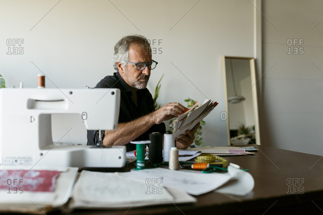 Mature tailor looking at fabric swatch papers while sitting at table in studio