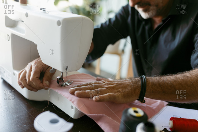 Male costume designer sewing fabric while working in studio