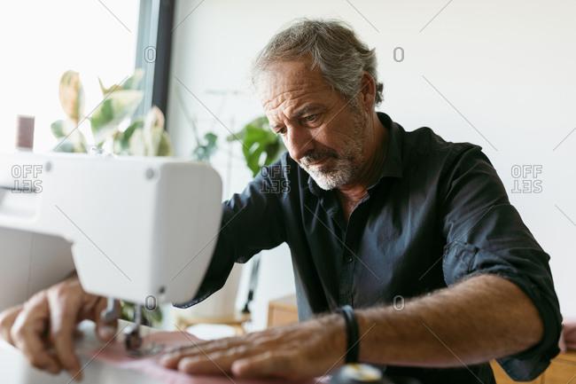 Male costume designer using sewing machine while working in studio