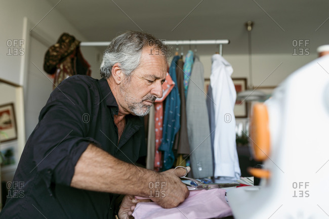 Talented mature male tailor cutting fabric with scissor at workplace