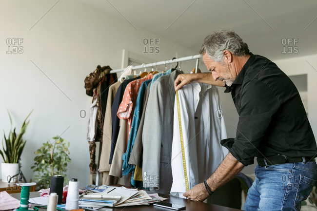 Mature male tailor measuring shirt with tape measure at work studio