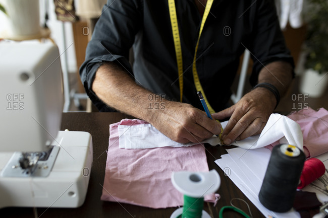 Male tailor marking on fabric with pencil at work studio