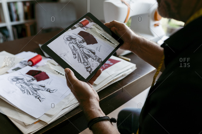 Male tailor photographing sketch through digital tablet at work studio