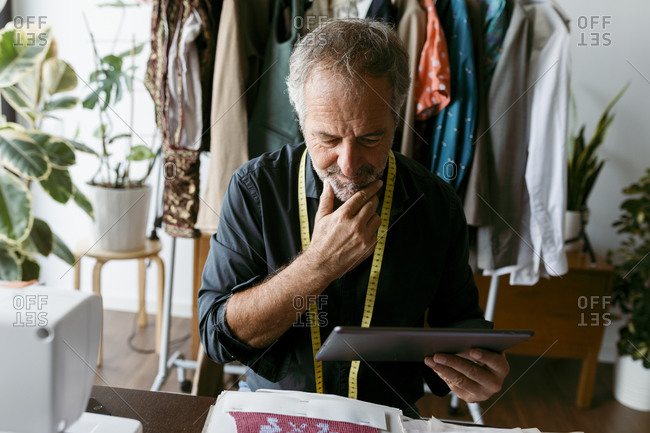 Mature male tailor thinking while looking at digital tablet in work studio