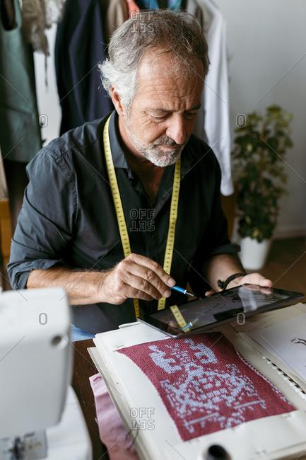 Male costume designer using digital tablet working at studio