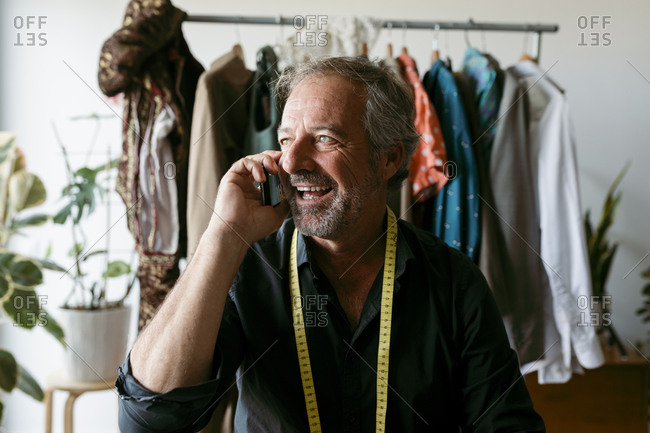 Happy male costume designer looking away while talking on mobile phone at work studio