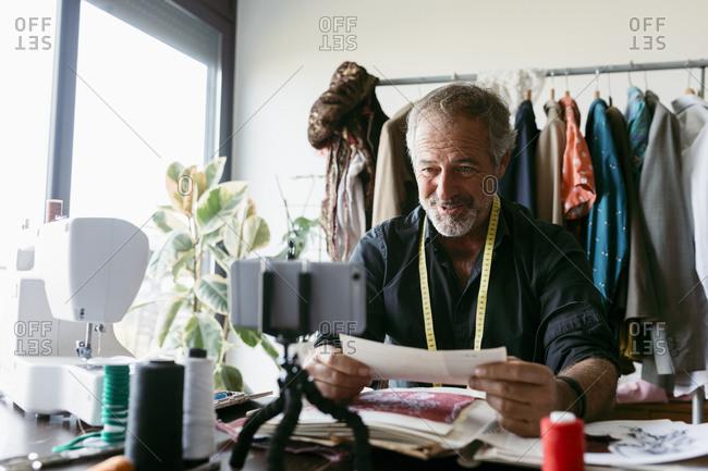 Smiling mature costume designer vlogging at work studio