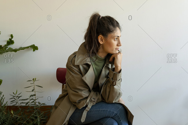 Thoughtful female model with hand on chin sitting against wall at home