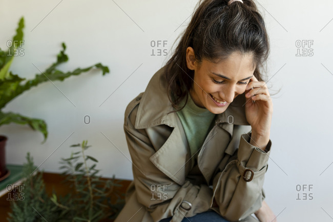 Smiling woman looking down while sitting against wall at home