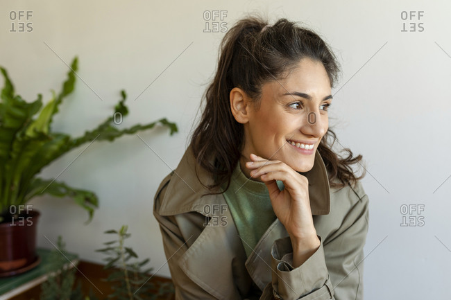 Smiling woman with hand on chin looking away sitting against wall