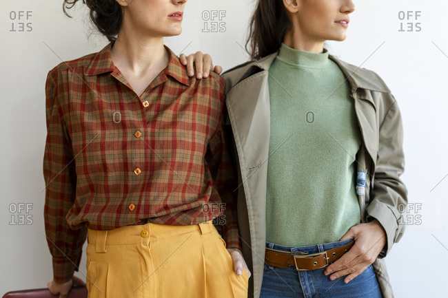 Female friends wearing retro style clothing standing against wall