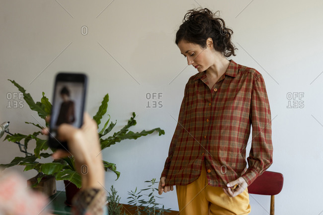 Woman taking photo of female model standing at home