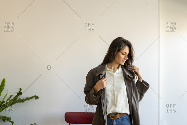 Beautiful woman wearing jacket standing against wall at home