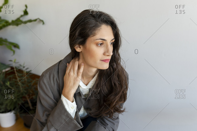 Thoughtful beautiful woman looking away while sitting at home