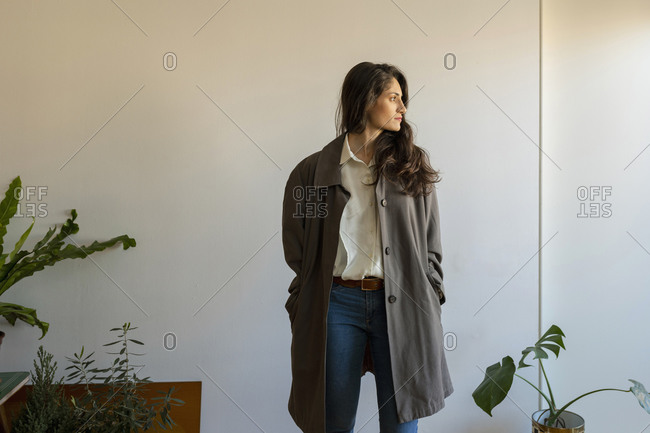 Female model with hands in pockets looking away while standing at home