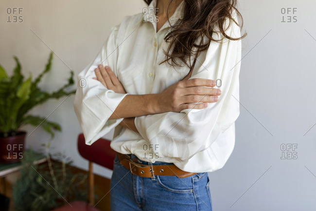 Woman wearing white shirt with arms crossed standing against wall at home