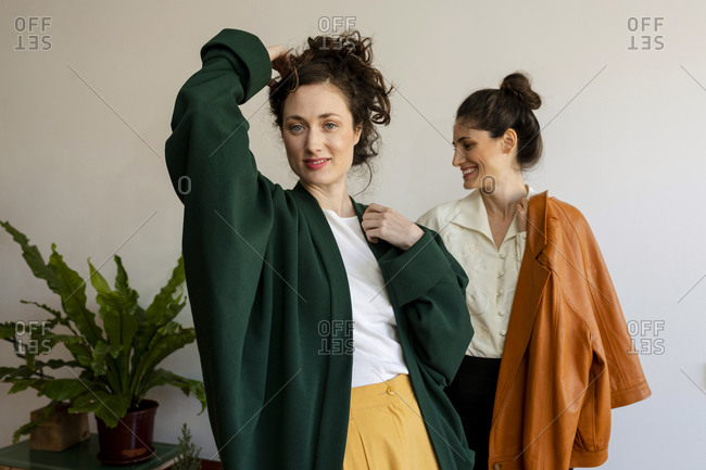 Beautiful woman with hand in hair standing with smiling female model at home