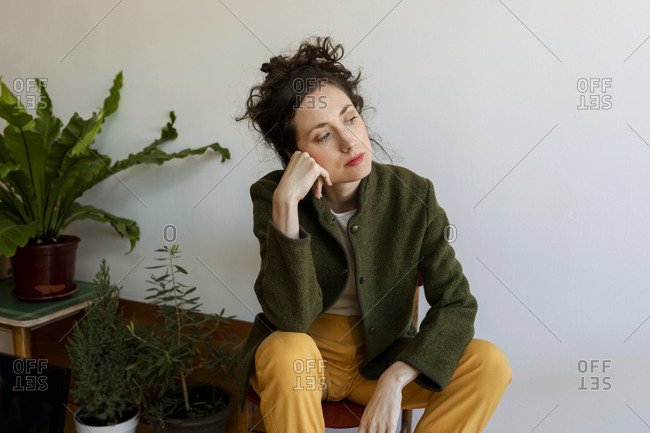 Thoughtful female model with hand on chin looking away while sitting against wall at home