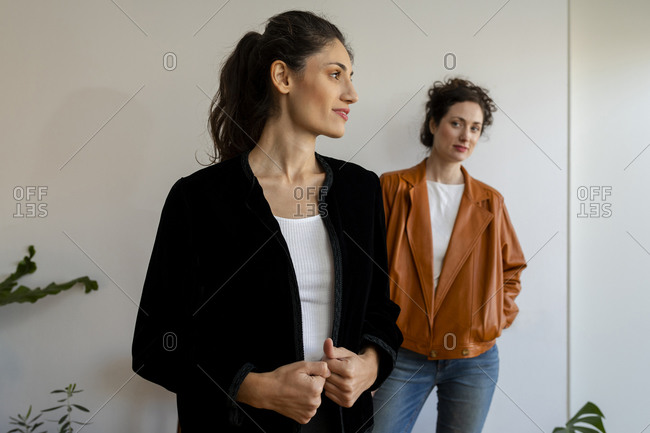 Female models wearing jacket standing against wall at home