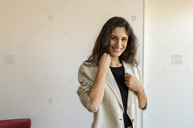 Happy female model wearing jacket standing against wall at home
