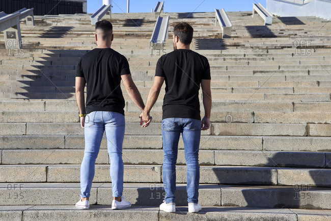 Homosexual couple holding hands while standing on steps during sunny day