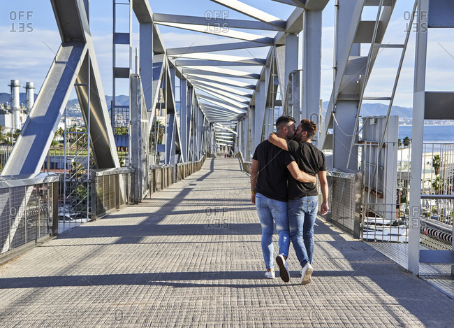 Homosexual couple kissing while walking on bridge during sunny day