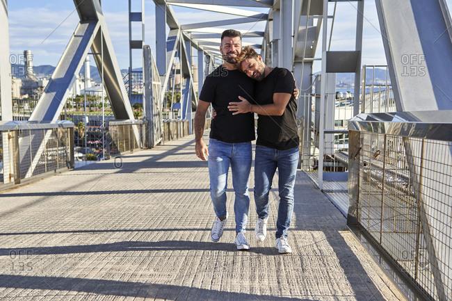 Gay man leaning on shoulder of boyfriend while walking on footbridge