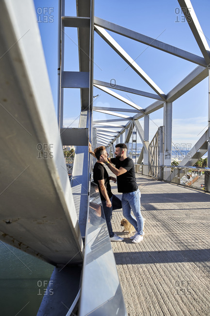 Happy homosexual couple spending time together on footbridge