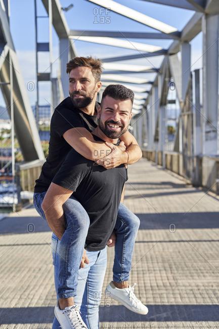 Smiling gay man piggybacking boyfriend on footbridge during sunny day