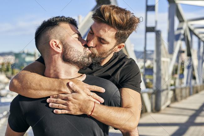Gay man kissing boyfriend on footbridge during sunny day