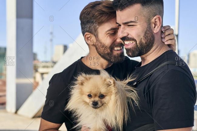 Happy homosexual couple with dog on footbridge