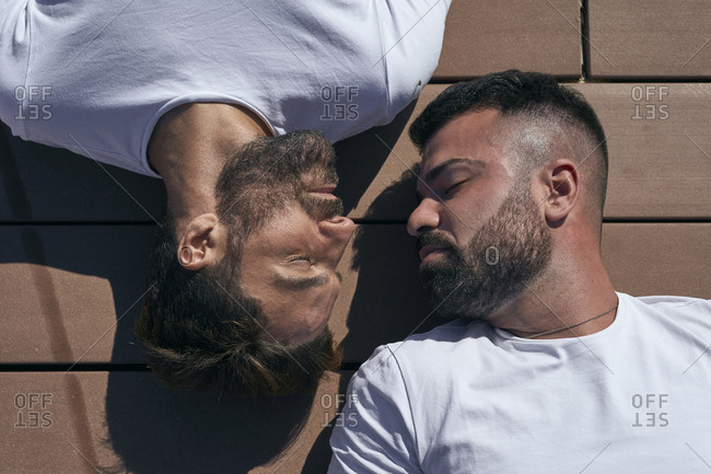 Homosexual couple lying on face to face on floorboard during sunny day