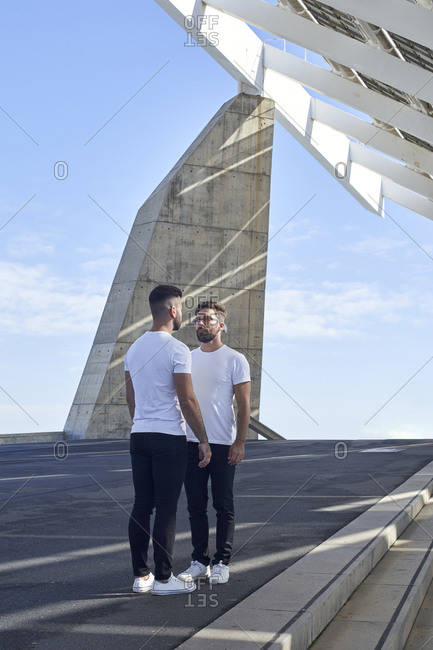 Homosexual couple looking at each other while standing at Parc del Forum- Barcelona- Spain
