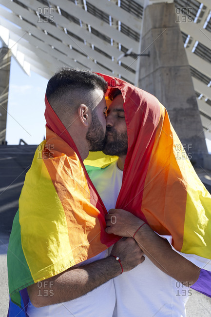 Homosexual couple covered in rainbow flag kissing during sunny day