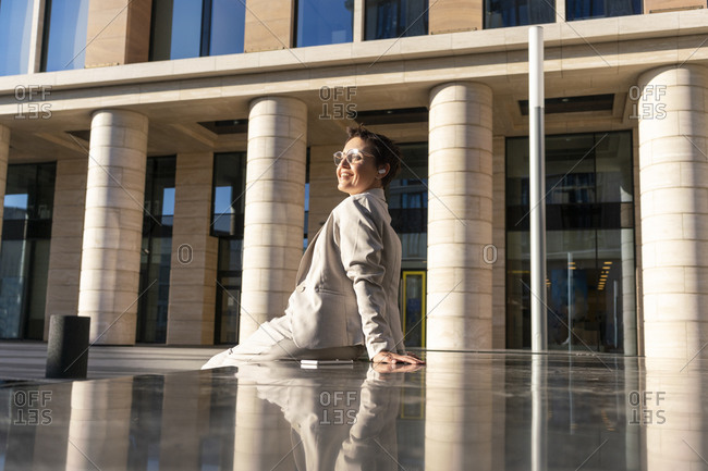 Businesswoman resting while sitting on bench against building