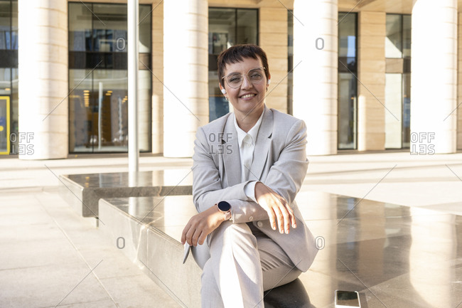 Businesswoman smiling while sitting on bench in city