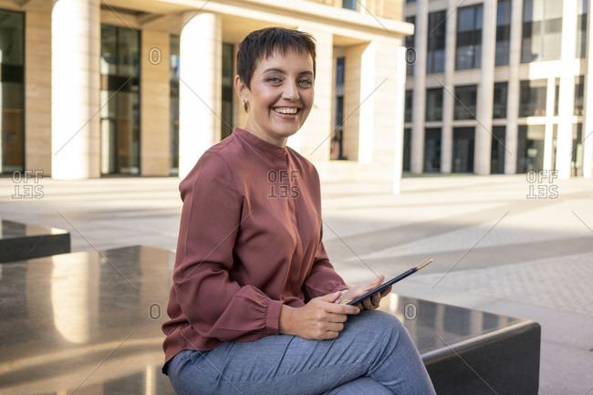 Smiling woman using digital tablet while sitting on bench in city