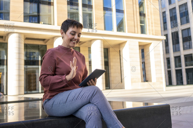 Woman waving hand to video call on digital tablet while sitting on bench against building
