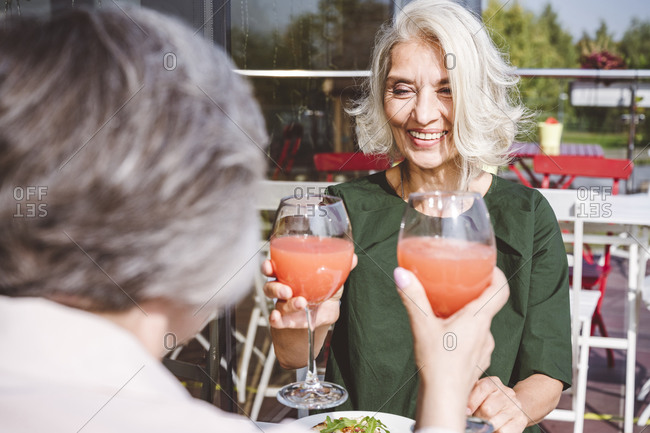 Smiling woman having juice with female friend at restaurant