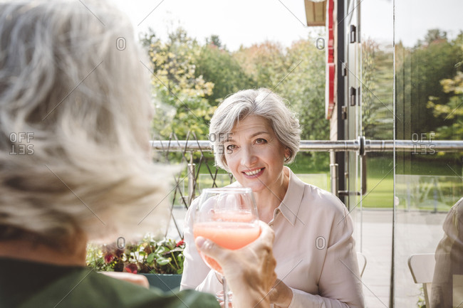 Female friends toasting drink while sitting at restaurant