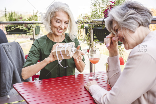 Smiling woman opening gift while sitting with female friend at restaurant