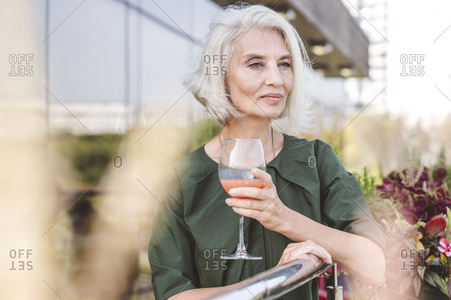 Mature woman drinking juice while standing by railing at restaurant