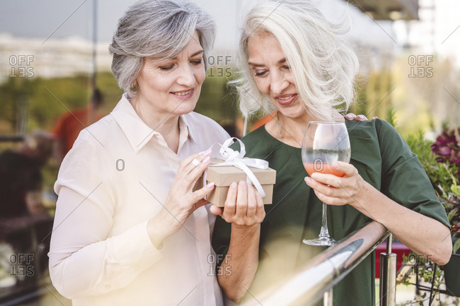 Friend giving gift to woman standing by railing at restaurant