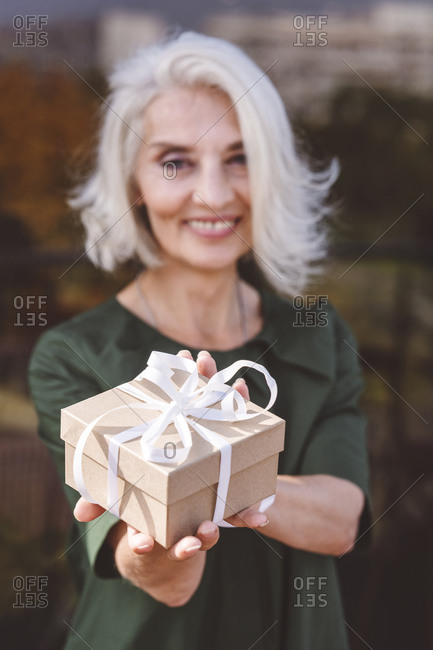 Smiling mature woman holding gift while standing at restaurant