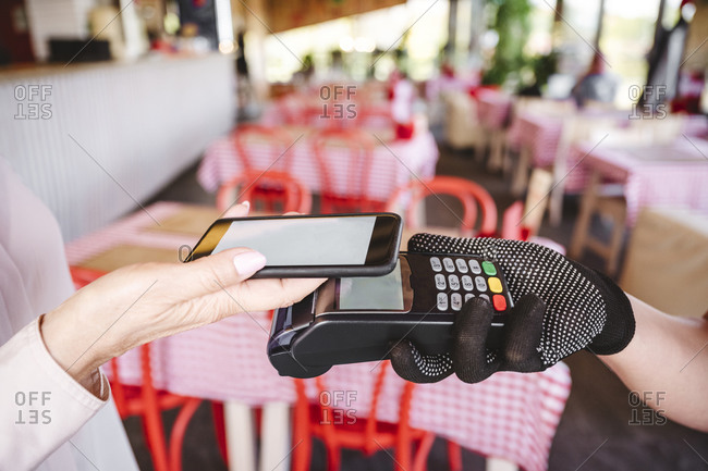 Mature woman paying bill through mobile phone while standing at restaurant