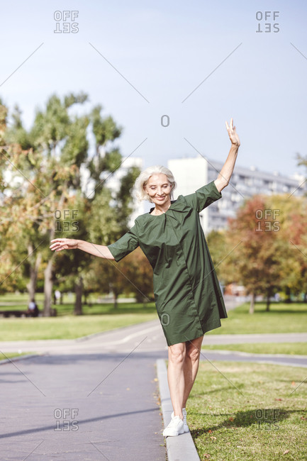 Playful mature woman walking balancing on edge of road in city