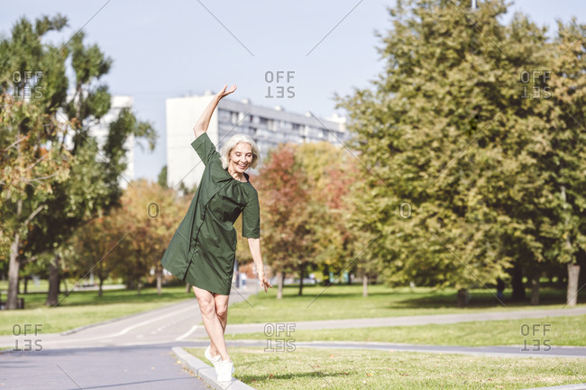 Smiling woman walking on edge of street in city