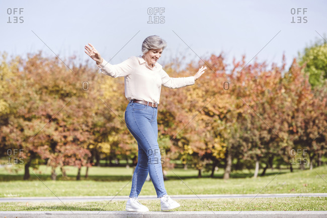 Smiling woman with arms outstretched walking on edge of street road at city