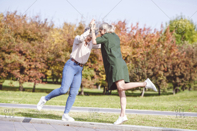 Playful women dancing while standing on road at park